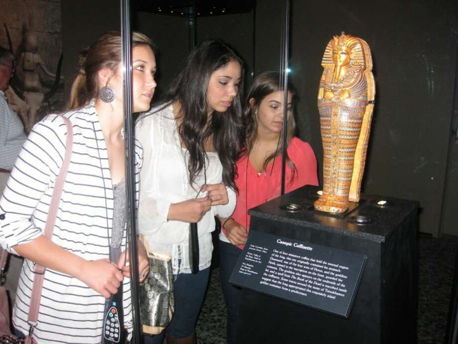 "Oak Ridge High School juniors Autumn Dorrough, left, Marcela Arias, right, and senior Raegan Jones admire a golden coffinette that once contained King Tut's stomach at the Houston's Museum of Fine Arts' exhibit ""Tutankhamun: The Golden King and the Great Pharaohs."""