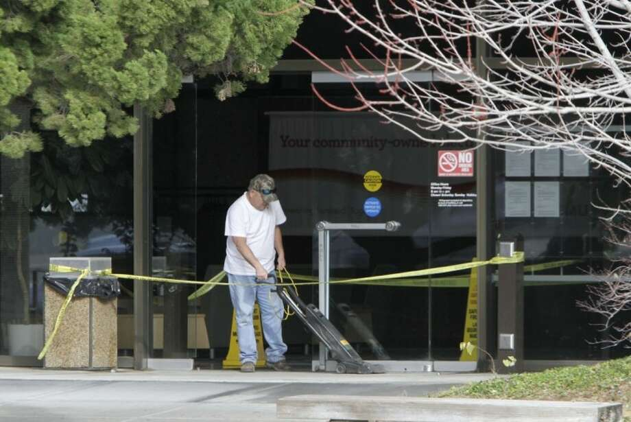 A worker cleans the front entrance to the Sacramento Municipal Utility District building Wednesday that was still cordoned off by police tape after a Tuesday night shooting that left two men dead, in Sacramento, Calif. Photo: Rich Pedroncelli