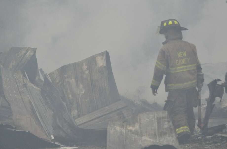 A firefighter clears debris after containing a fire north of Porter on Sunday.