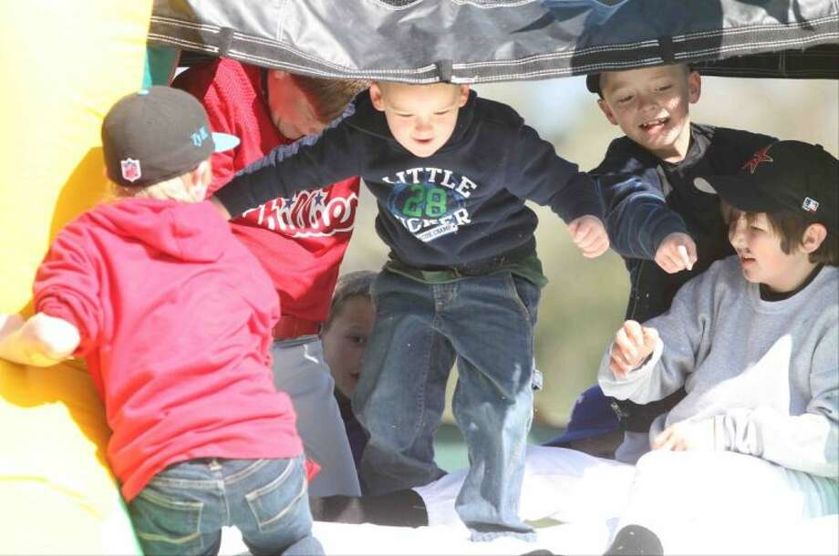 Micah Chathman, 4, enjoys an inflatable slide during Opening Day at the ORWALL baseball fields Saturday. Photo: Jason Fochtman