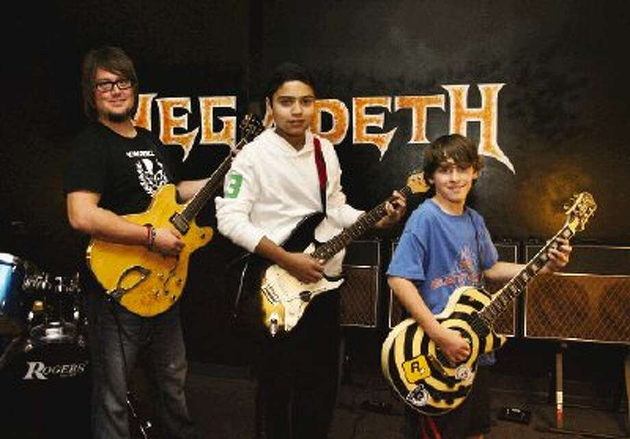 School of Rock General Manager and Music Director Marc Reczek, left, works with Martin Escobar, 14, and Tyler Dohmen, 13, on their rock technique.