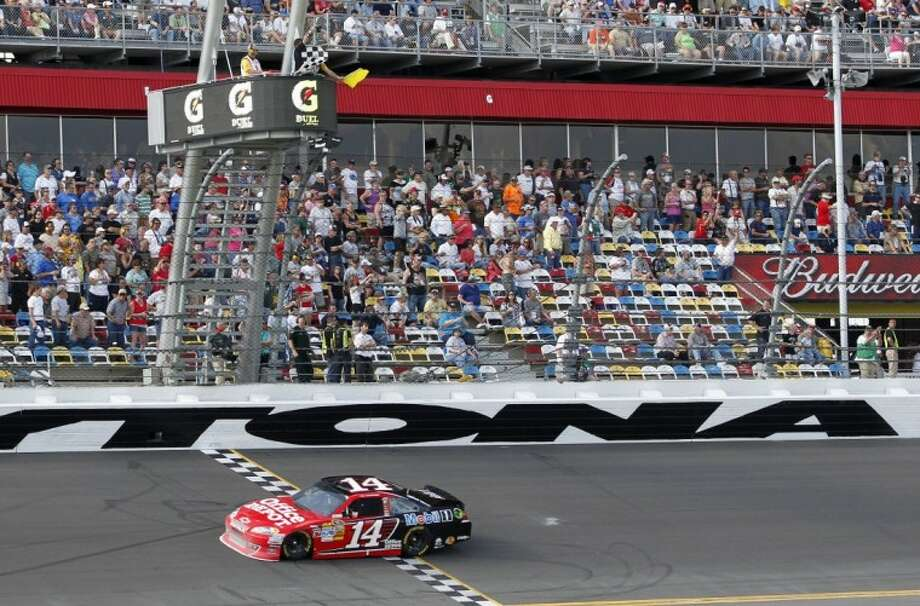 Tony Stewart crosses the finish line under caution to win the first of two NASCAR Daytona Gatorade Duel 150 qualifying auto races in Daytona Beach, Fla., Thursday. Photo: Terry Renna Chuck McQuinn