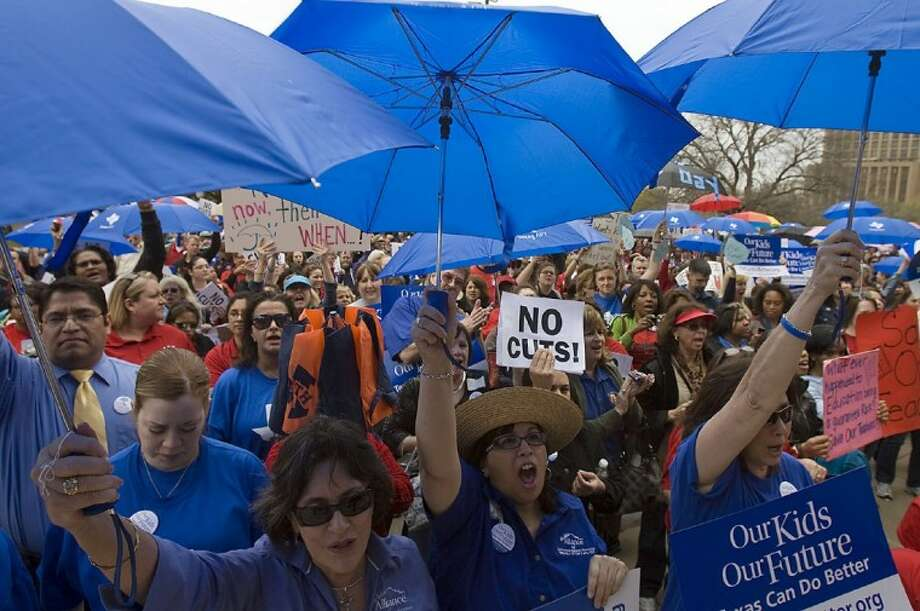 From left, Elda Flores, with San Antonio Alliance for Teachers and Support Personnel, Mary Jane Gonzalez, center, and Cathy Hazzard, both teachers at San Antonio Independent School District's Longfellow Middle School in San Antonio, hold up umbrellas during a rally held at the State Capitol in Austin on Monday.