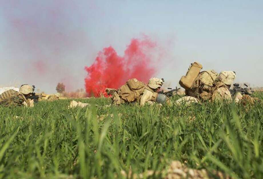 U.S. Marines from 3rd Battalion, 6th Marine Regiment take cover in an open poppy field during a firefight as Taliban fighters fire on them in the town of Marjah in Afghanistan's Helmand province on Monday. / AP2009