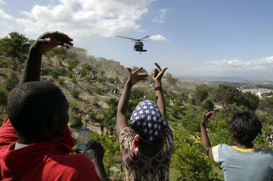People gesture as a U.S. helicopter makes a water drop near a country club used as a forward operating base for the U.S. 82nd Airborne Division in Port-au-Prince, Haiti, Saturday. Relief groups and officials are focused on moving aid flowing into Haiti to survivors of the powerful earthquake that hit the country on Tuesday. / AP2010
