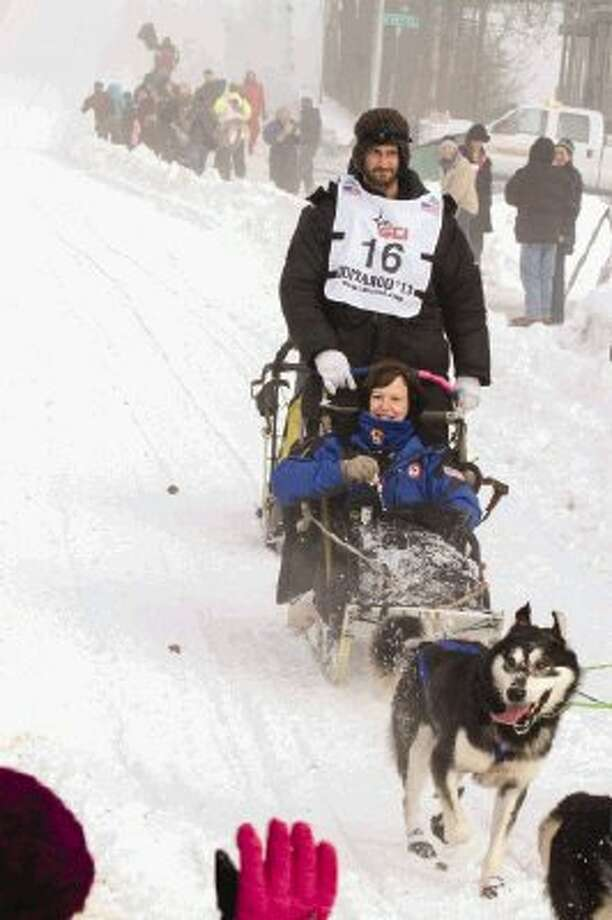 Barbara Cargill, State Board of Education Chair, rides in the dog-sled team of Musher Nicolas Petit last weekend in Alaska during the ceremonial launch of this year's Iditarod race. (Photo by John Gomes)