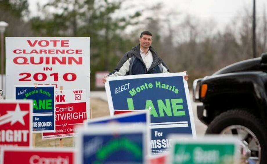 Candidate Monte Lane holds a campaign sign as he greets motorists entering the East Montgomery County Annex Friday in New Caney. A Precinct 4 Constable's officer has filed a complaint against Lane's wife for allegedly striking him with a campaign sign. / The Courier