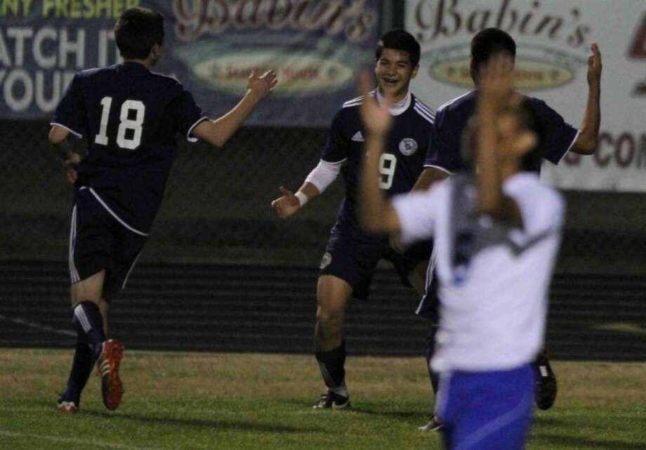 College Park's Rene Carbajal (19) celebrates with teammates after scoring a goal as Oak Ridge's Alec Burmister reacts during Tuesday's match at Oak Ridge High School. To view or purchase this photo and others like it, visit HCNpics.com. Photo: Jason Fochtman