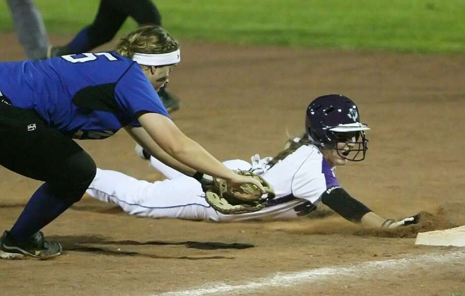 Willis' Hope Estes dives back safely to first base to avoid being picked off by New Caney's Sarah Upchurch during Friday night's game in Willis.