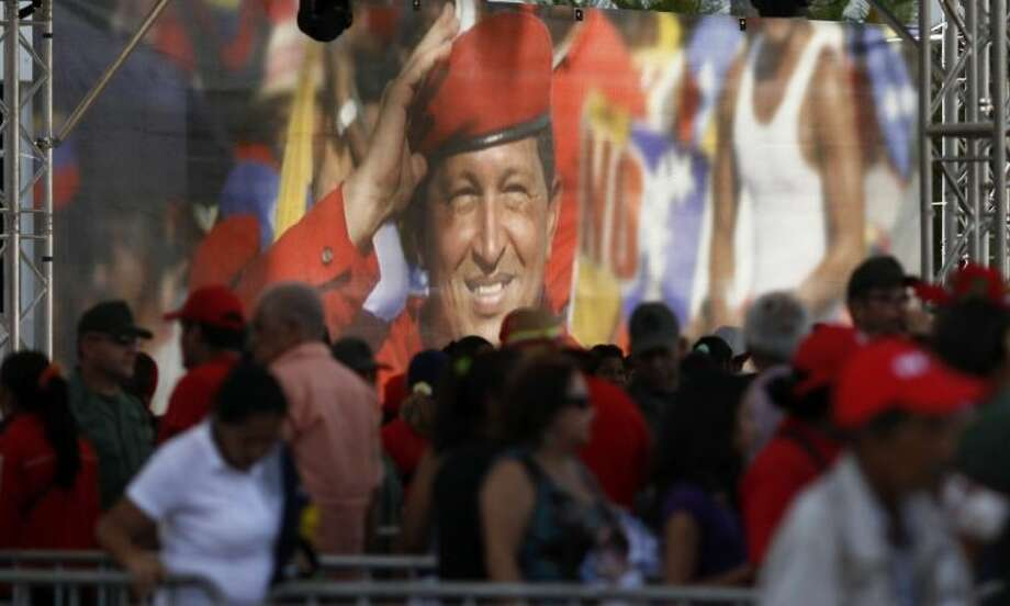 A large image of Venezuela's late President Hugo Chavez is on display where mourners line up to view his body lying in state at the military academy in Caracas Thursday. Photo: Ariana Cubillos