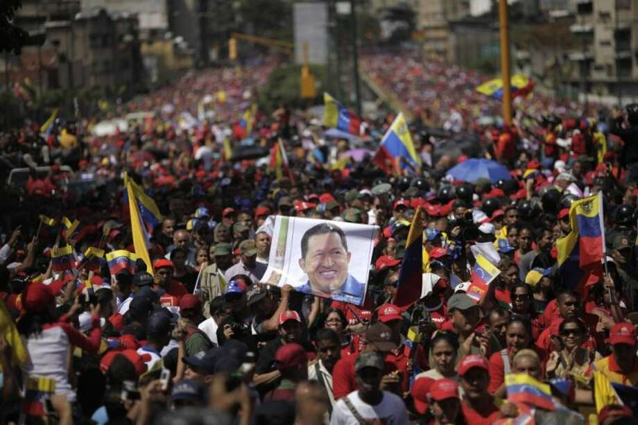 Supporters of Venezuela's late President Hugo Chavez walk behind his coffin as it is paraded through the street from the hospital, where he died on Tuesday, to a military academy in Caracas, Venezuela, Wednesday. Photo: Rodrigo Abd