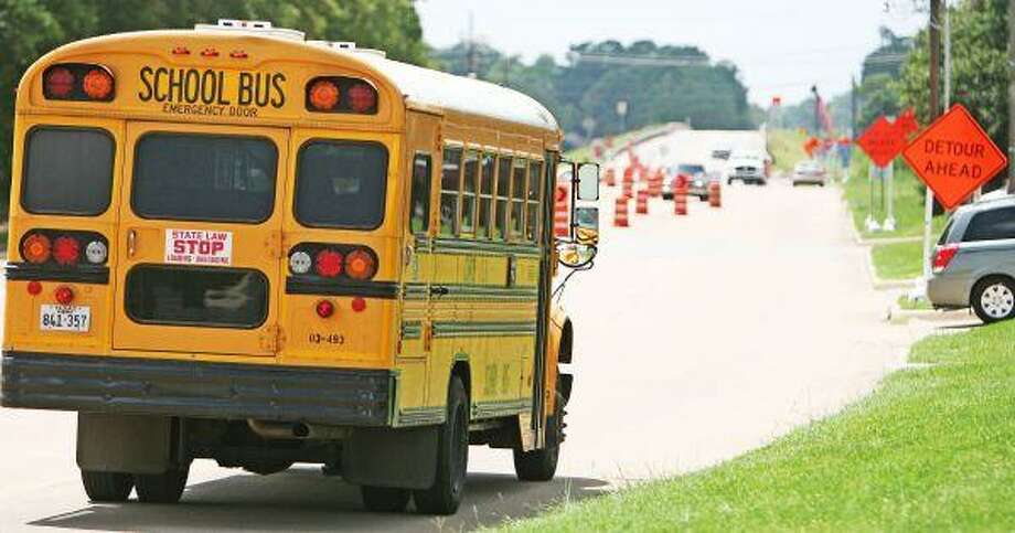 A Conroe ISD school bus drives through construction on Gladstell Road. Construction is an issue CISD bus drivers must navigate as the school year begins Monday. / Staff