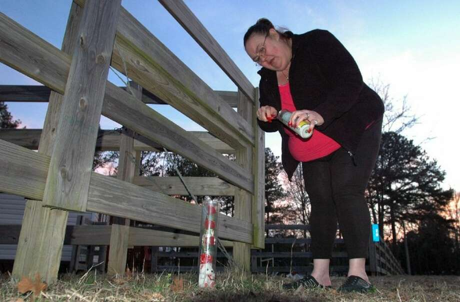 Gail Denny places a candle and stuffed animal outside the home of 9-year-old Savannah Hardin near Attalla, Ala. Authorities say Hardin was forced to run for three hours as punishment for having lied to her grandmother about eating candy bars. The severely dehydrated girl had a seizure and her death days later was ruled a homicide. Photo: Jay Reeves