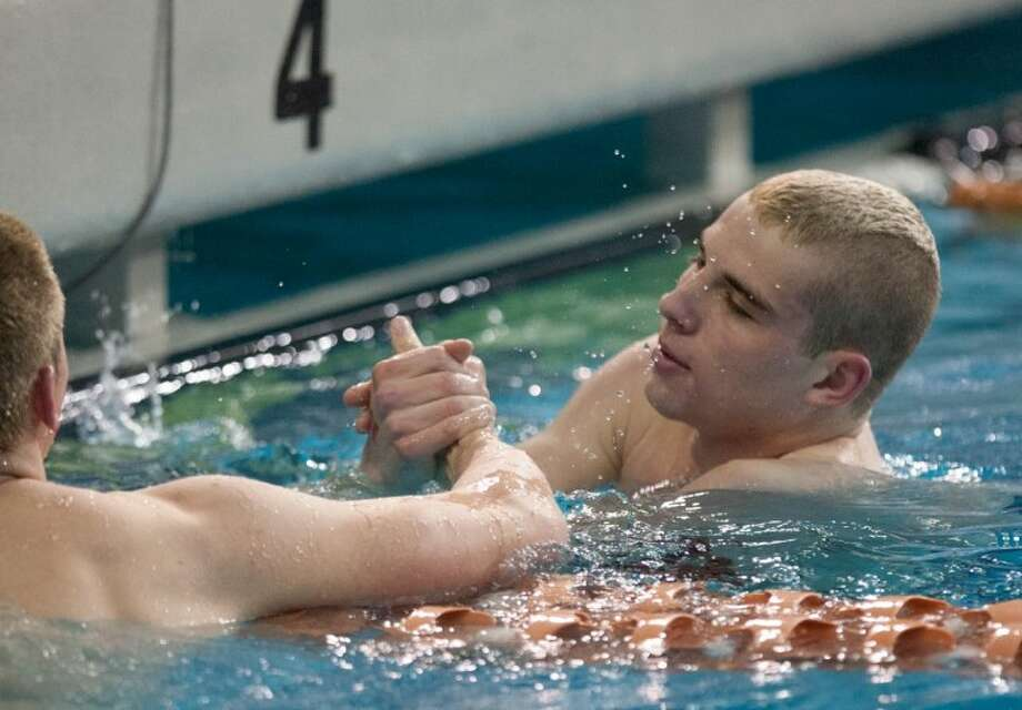 College Park Swimmer Gray Umbach, right, shakes hands with fellow competitor Jonathan Debaugh, of Conroe High School, after the Boys 100 Yard Butterfly Event during Saturday's 5A State Swimming and Diving Finals at the Lee & Joe Jamail Texas Swimming Center in Austin. Photo: Staff Photo By Eric S. Swist