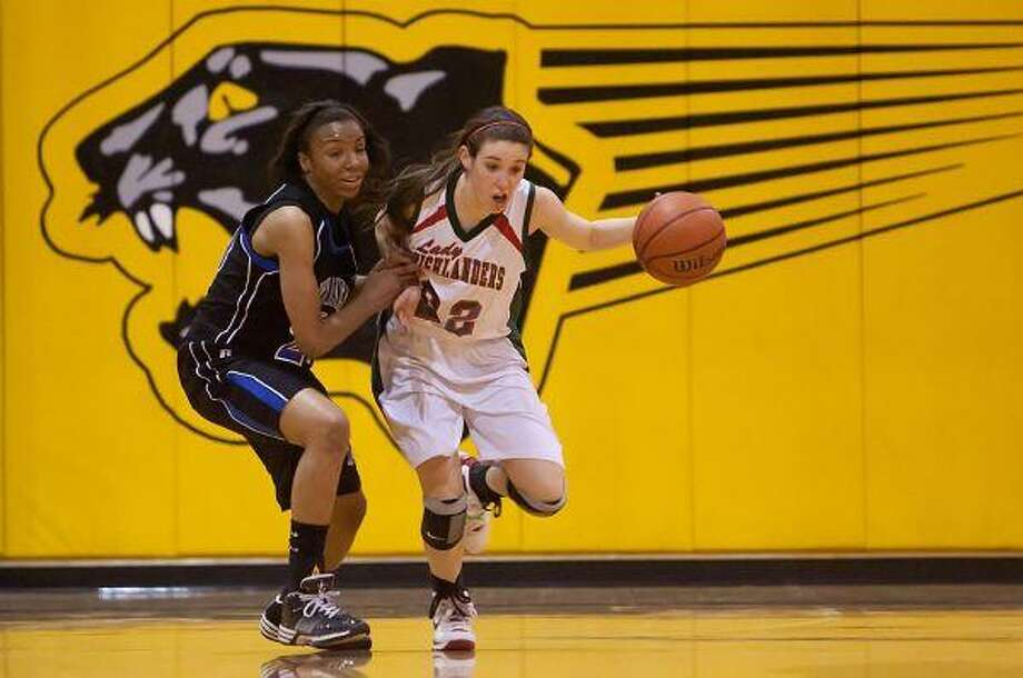 The Woodlands' Paige Bradley dribbles against a Dekaney defender during Monday night's playoff game at Klein Oak High School. / The Courier