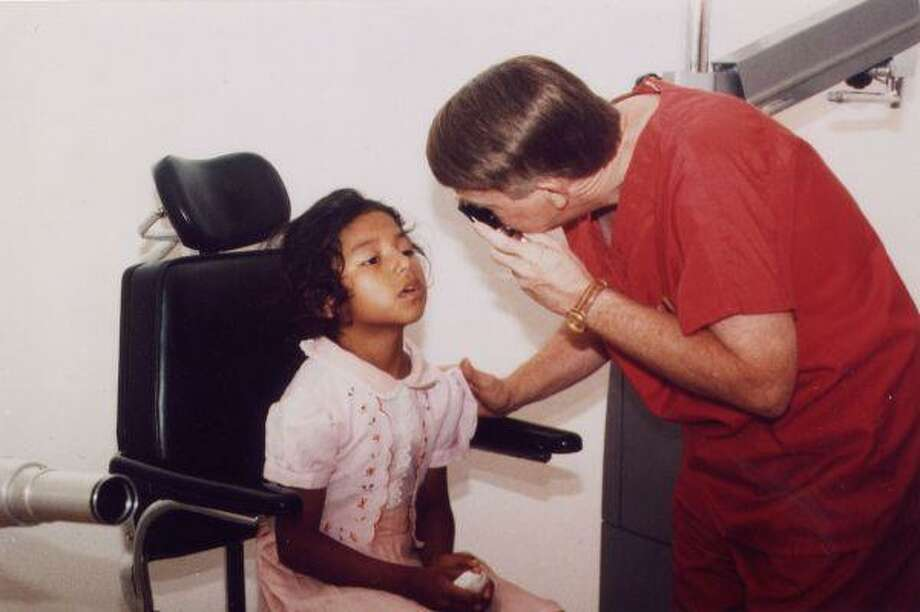 Dr. Downey Price, founder of Benevolent Missions International, administers an eye exam to a young girl in El Salvador during a BMI trip. More than 40,000 men, women and children have received free eye care since the foundation of BMI, Price said.