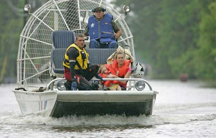Merri Embry holds her 2-year old daughter as Montgomery County Sheriff's deputies bring the pair to safety after performing a water rescue on Fairview Drive in the subdivision of Chateu Woods in Conroe on Tuesday. / AP