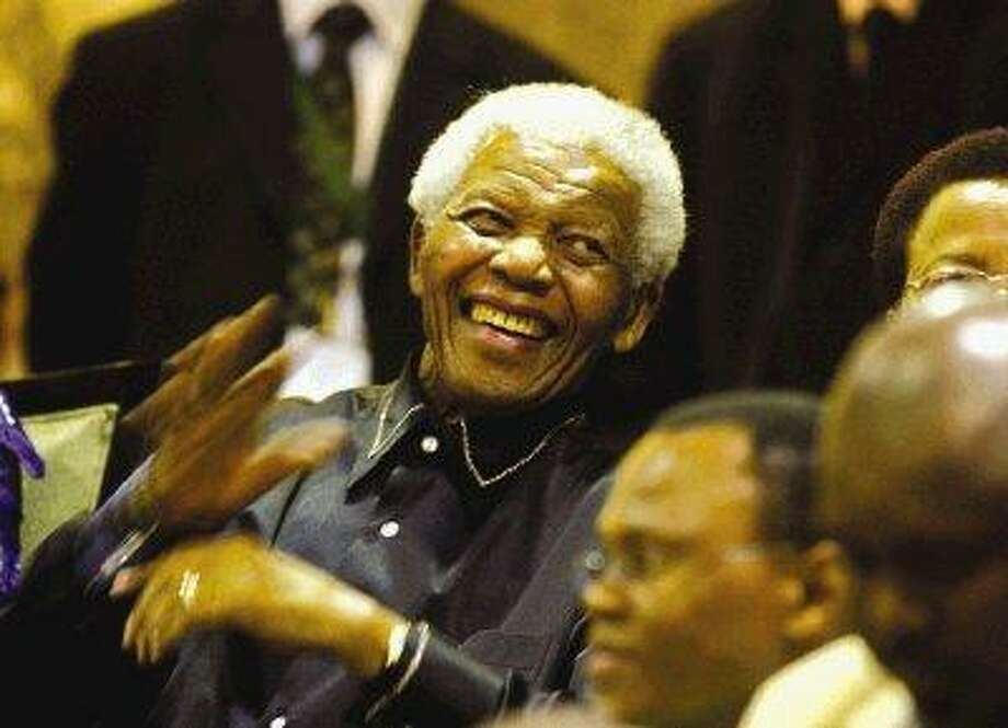 Former South African president Nelson Mandela waves inside Parliament at Cape Town, South Africa, Thursday. South African lawmakers sang Nelson Mandela's praises Thursday as the anti-apartheid icon settled into parliament's public gallery for a State of the Nation address scheduled in tribute to his 20 years of freedom. / AP2010