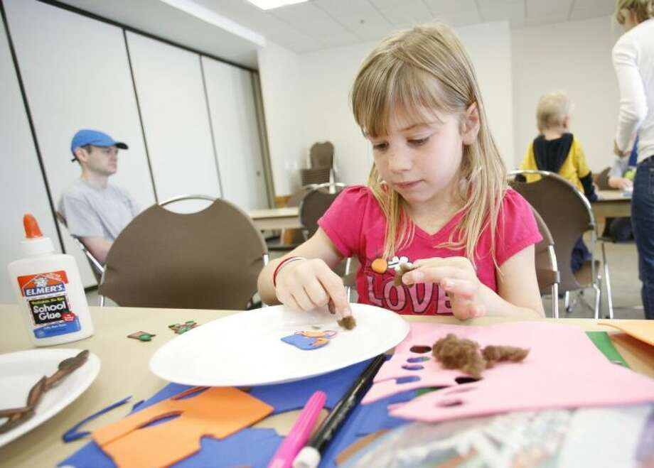 Abby Stofer, 7, of The Woodlands, works on making a paper plate bluebird nest during Saturday's Family Adventure Day at the Creekside YMCA. Photo: Staff Photo By Eric Swist