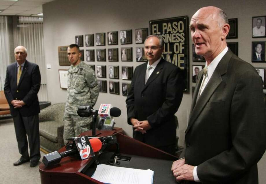 El Paso Mayor John Cook, right, presents a report that says Ft. Bliss has a $6 billion economic impact from automatic budget cuts during a news conference Friday in El Paso. Photo: Juan Carlos Llorca