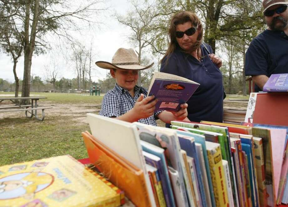 Dawson Clark, 7, smiles as he flips through books available for children during Saturday's Texas Legacy Catfish Festival at Tamina Park. Children attending the event received one free book. Photo: Staff Photo By Eric Swist