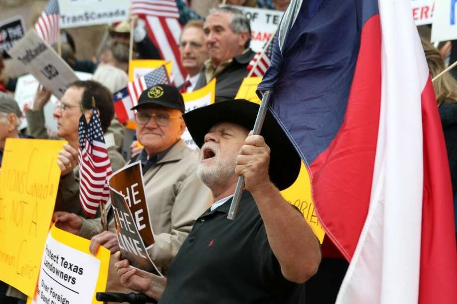 Eddy Radillo, of Yantis, sings and holds a Texas flag and a sign opposing the Transcanada Keystone Pipeline Feb. 17 outside of the Lamar County Courthouse in Paris, Texas, before a restraining order hearing. Property-rights activists rallied to protest a TransCanada suit to condemn private land in Northeast Texas for the Keystone pipeline right of way. Photo: Sam Craft