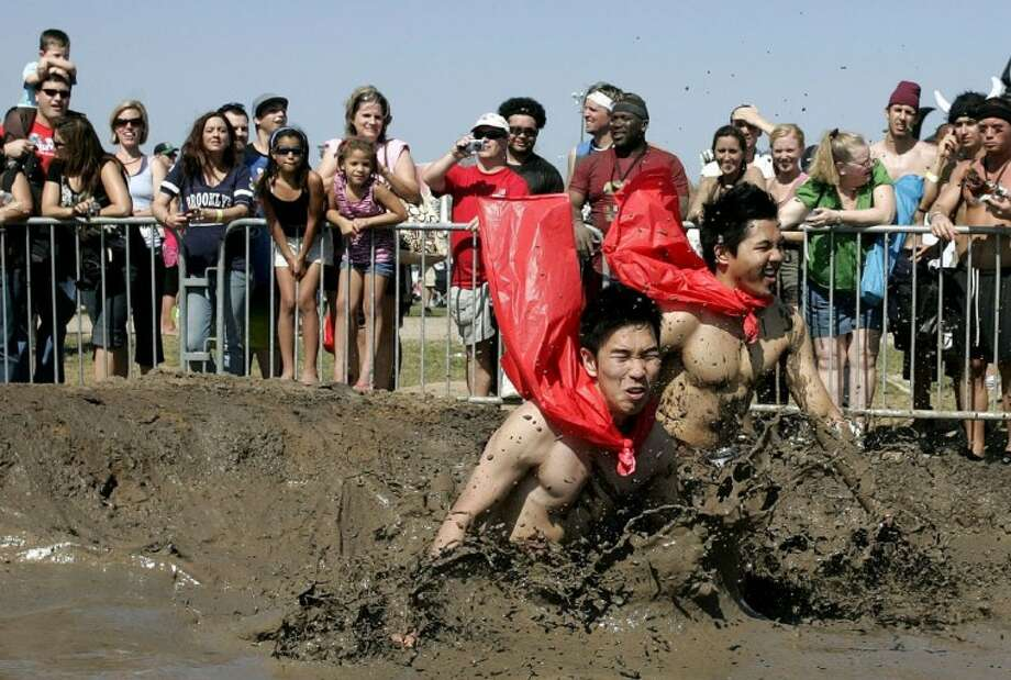 Spectators watch as a pair of participants plunge into the mud pit as they reach the final stretch of Saturday's Warrior Dash event held at the 3 Palms Extreme Sports Park in Conroe.