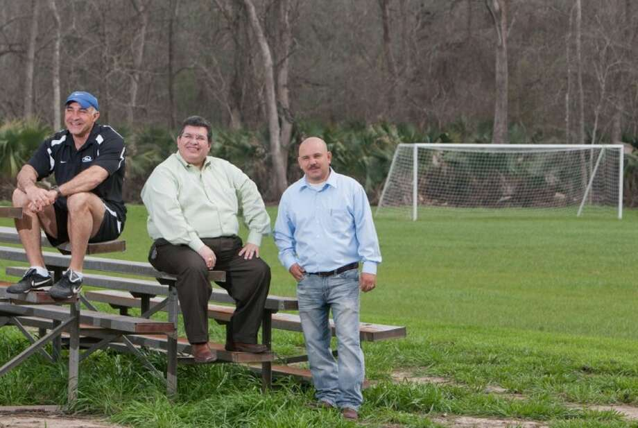Milton Arraez, Texas Rush director of coaching for senior girls, left, sits for a portrait with Abel Guerrero, center, and Juan Garza at one of the new fields at the Superior Soccer Complex off FM 1488 in Magnolia. The fields will be utilized by Texas Rush Soccer, which is expanding in the area.