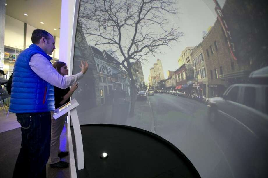 Katie Hinton, back, shows Russell Hamilton how to use the AT&T Teleporter at the SXSW Interactive Festival on Monday, in Austin. The device displays images of popular Austin attractions and places and allowed users to move the images with hand motions. Photo: Deborah Cannon
