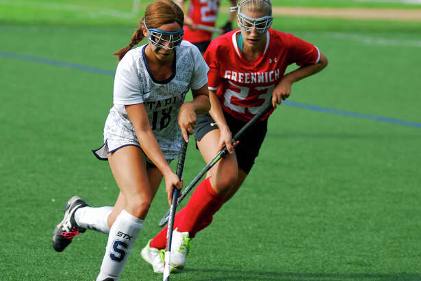 Staples' Alexis Bernard and Greenwich's Sammy Gould battle for possession during a field hockey game on Saturday, September10th, 2016.