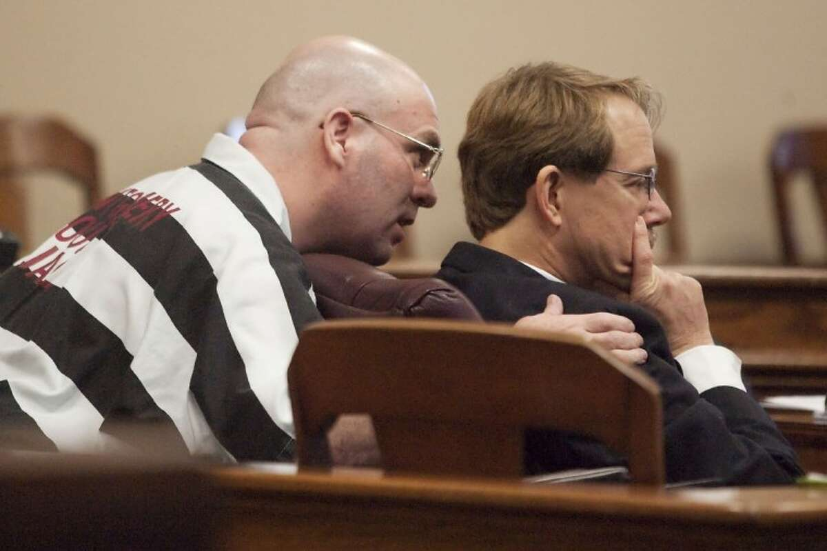 Larry Ray Swearingen, left, speaks to one of his attorneys, James Rytting, during a hearing Monday at the Montgomery County Courthouse.