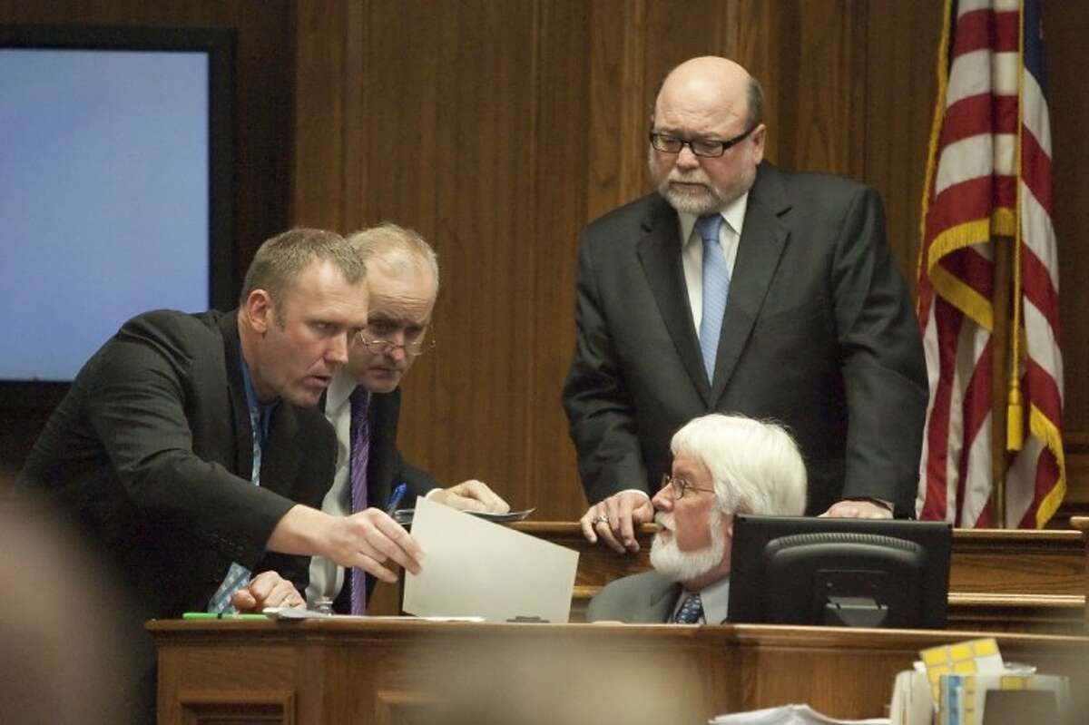 Prosecutor Warren Diepraam, left, and defense attorney Stephen Jackson examine photographs of maggots with Dr. Lee Goff, director of Forensic Sciences at the University of Honolulu, while Judge Fred Edwards looks on during an evidence hearing for Larry Ray Swearingen Monday at the Montgomery County Courthouse.