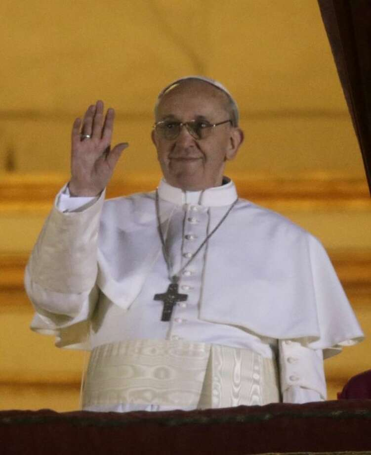 Pope Francis waves to the crowd from the central balcony of St. Peter's Basilica at the Vatican Wednesday. Cardinal Jorge Bergoglio, who chose the name of Francis, is the 266th pontiff of the Roman Catholic Church. Photo: Gregorio Borgia