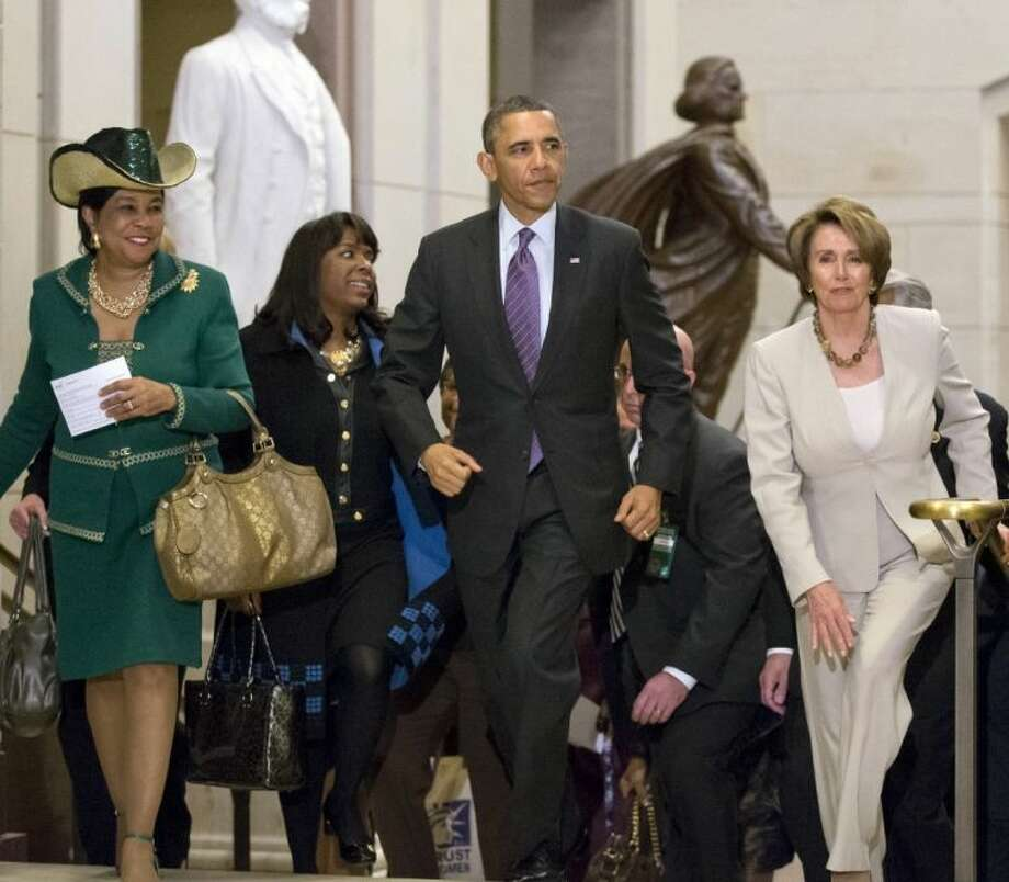 President Barack Obama and House Minority Leader Nancy Pelosi, D-Calif., leave a meeting with House Democrats at the Capitol, in Washington, Thursday. At far left is Rep. Frederica Wilson, D-Fla., with Rep. Terri Sewell, D-Ala., second from left. Photo: J. Scott Applewhite
