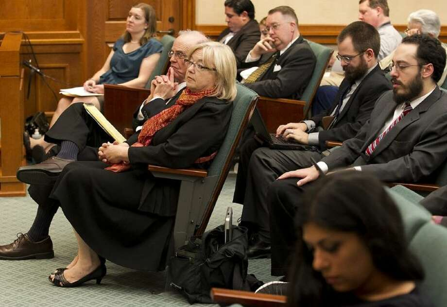 Claire Wilson James, a survivor of the Charles Whitman University of Texas Tower shootings, foreground left, waits to testify before a packed committee room Thursday in Austin. James urged Texas lawmakers Thursday to reject proposals that would allow concealed handgun license holders to carry their weapons into college buildings and classrooms. Photo: Ralph Barrera