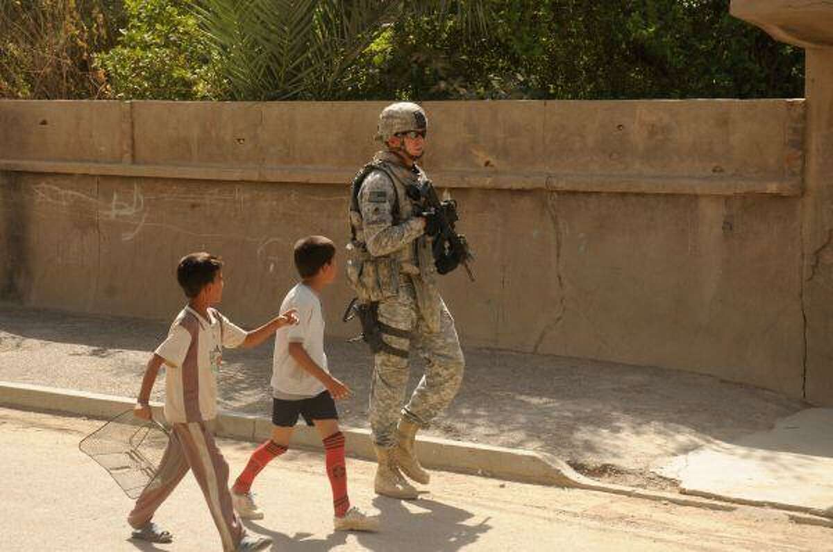 Two Iraqi children follow U.S. Army Staff Sgt. Matt Radcliffe, of Spring, down one of the streets of Baghdad. Radcliffe handles security duties with the 3rd Brigade Combat Team, 4th Infantry Division, Multi-National Division. Now on his second deployment in Iraq, the 2002 Oak Ridge High School graduate has about five or six months left before coming home to Texas.