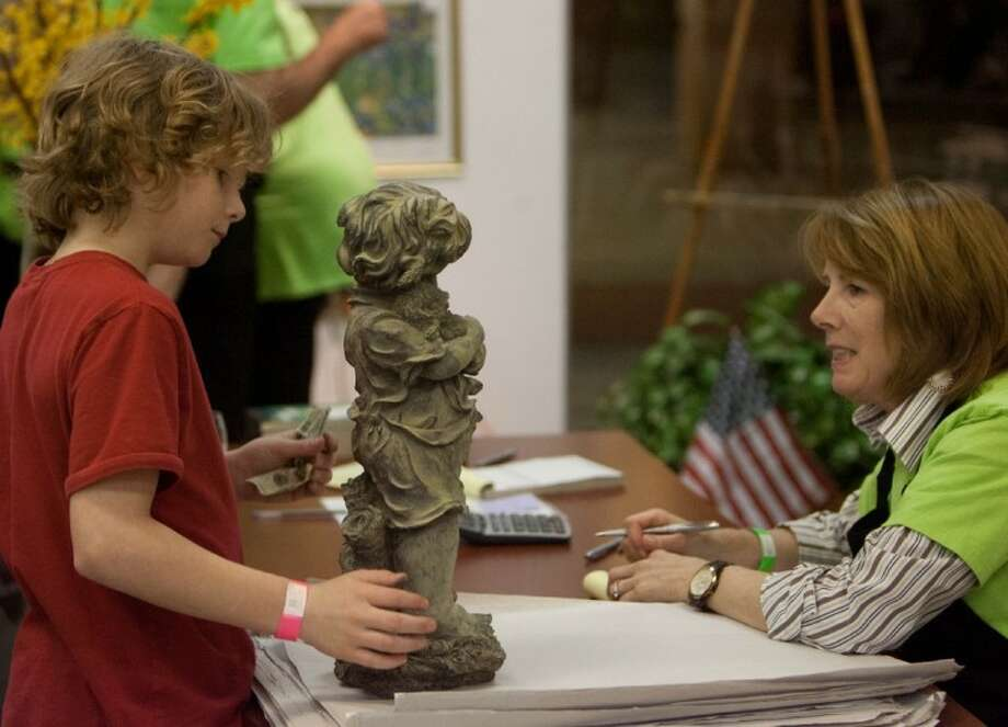 A young boy purchases a statue during the Jazzy Junque preview party and early bird shopping Wednesday night at the Outlets at Conroe. The sale runs from today through Sunday and offers a variety of items. Photo: Staff Photo By Eric S. Swist