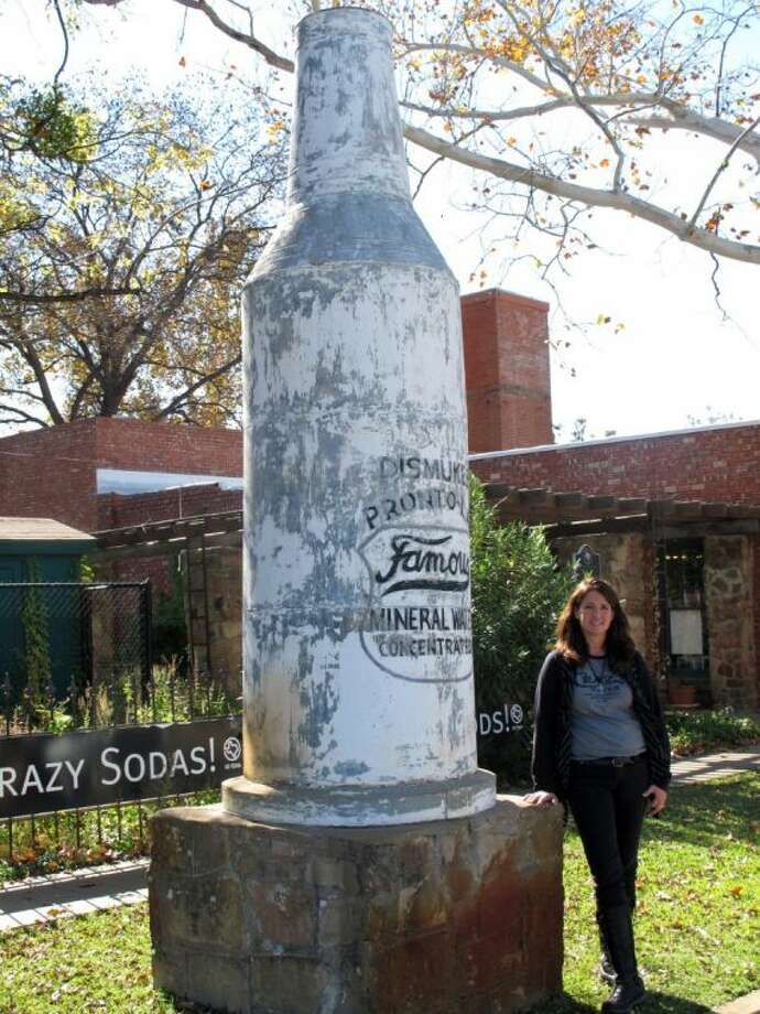 In this Nov. 14, 2012 photo, Carol Elder, owner of Famous Water Co., stands by a monument outside her company in Mineral Wells, Texas. In the early 1900s, tens of thousands flocked to the small Texas town to soak in mineral baths at hotels and drink local wells' natural mineral water. Elder's is the only water company still in business and now sells Crazy Water in seven states. Photo: Angela K. Brown