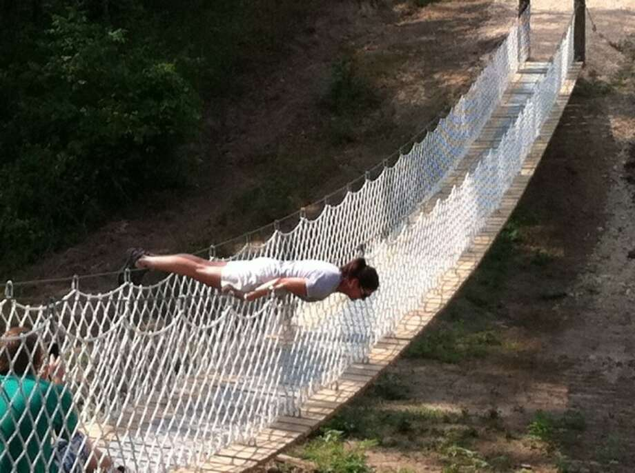 Sandra Huskey planks on a rope bridge over a dry creek in Huntsville. She said it looked more dangerous than it was, but the steel ropes were painful in that position.