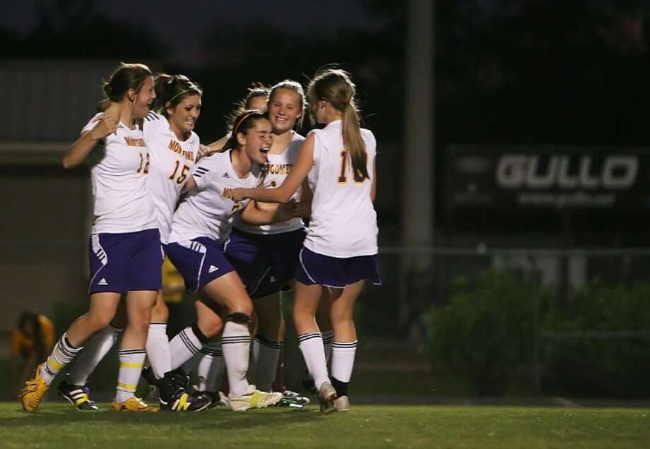 Montgomery's Amy Anderson, center, celebrates her extra time goal with teammates during Thursday night's Region III-4A bi-district playoff game against Waller at Magnolia High School.