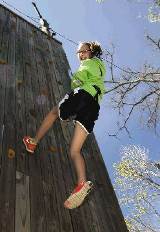 Ann Rabich, 12, of Conroe is all smiles climbing the vertical wall at the Conroe Family YMCA on the first day of spring break.