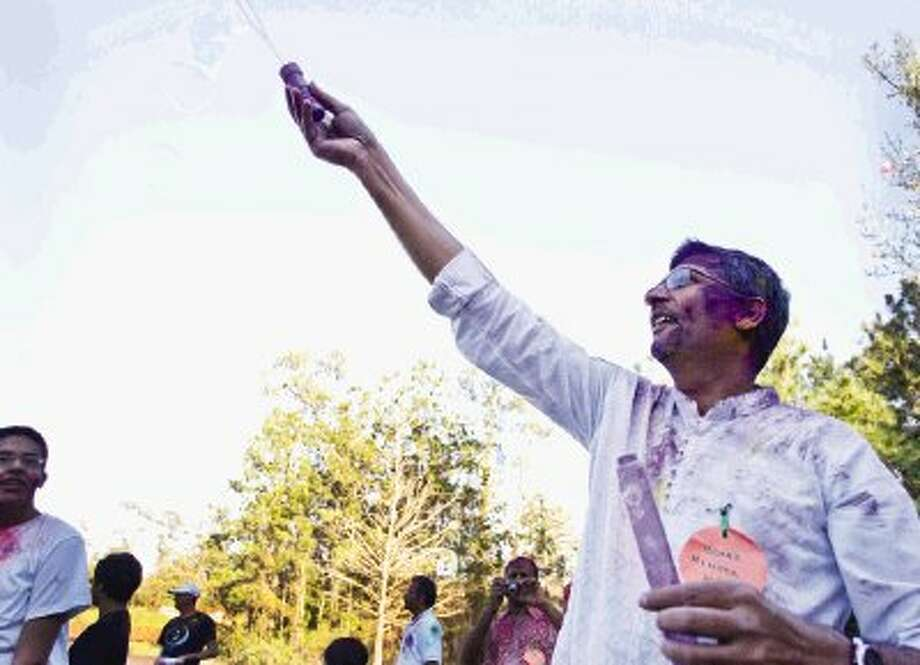 "Jit Chudasama, a board member of The Woodlands India Association, spreads bubbles as association members celebrated Holi, known as ""the festival of colors"" which celebrates the advent of Spring, on Saturday at Alden Bridge Park in The Woodlands."