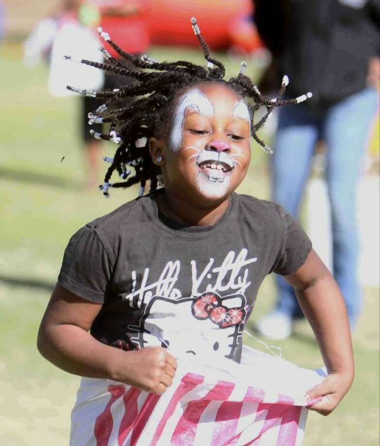Breniyah Maxcy's braided hair flies as she competes in a sack race at the Mr. Bunny event at Kasmiersky Park Saturday in Conroe. Children enjoyed face painting, sack races, balloon animals and getting to hold bunnies at the annual event. Photo: Staff Photo By Jason Fochtman