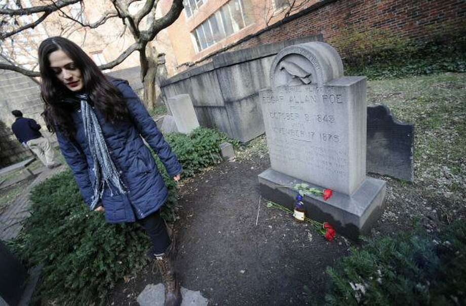 Cynthia Pelayo, of Chicago, leaves roses and cognac at the burial site of Edgar Allen Poe Tuesday in Baltimore. She left the roses and cognac after a mysterious visitor who has left roses and cognac at the grave of Edgar Allan Poe each year on the writer's birthday failed to show early Tuesday, breaking with a ritual that began more than 60 years ago. / AP2010