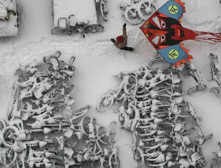 A child flies a kite at a snow-covered bicycles parking place in Beijing. Some Chinese factories were ordered to shut down to ensure sufficient power to heat homes as demand surged amid record-setting winter cold, a utility company said. For more about the weather worldwide, turn to the story on Page 8A / COLOR CHINA PHOTO