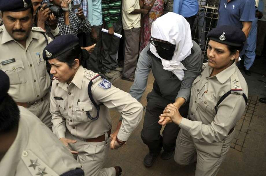 A Swiss woman, center, who, according to police, was gang-raped by a group of eight men while touring by bicycle with her husband, is escorted by policewomen for a medical examination at a hospital in Gwalior, in the central Indian state of Madhya Pradesh, Saturday. Photo: Uncredited