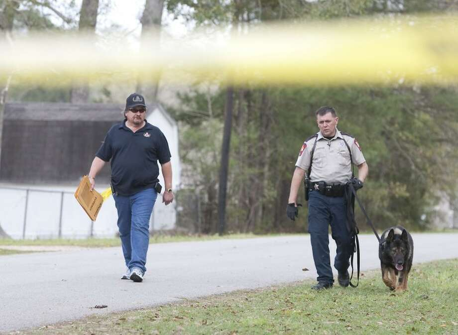 A Montgomery County Sherif's Deputy searches for drugs thrown from a vehicle near the intersection of Morgan Drive and Bates in Splendora on Tuesday. Photo: Karl Anderson