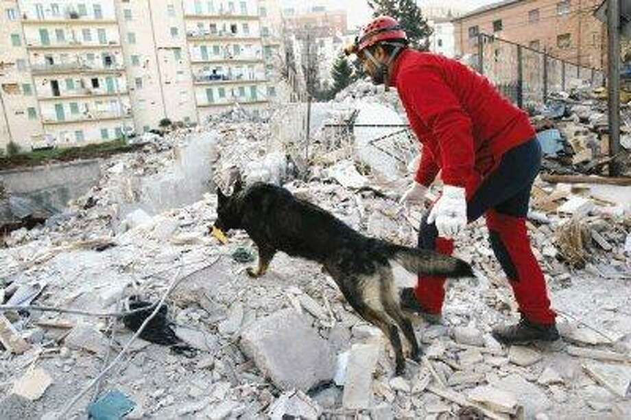 A member of a Spanish rescue team and a dog search through rubble in L'Aquila, central Italy, Wednesday. The death toll in Italy's quake has risen to 250, officials said Wednesday, as strong aftershocks cause further fear among residents sheltered in tent camps. / AP