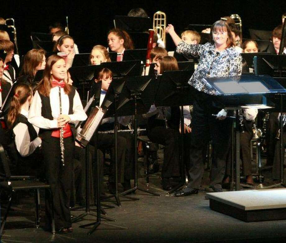 "Charlotte Randall, guest clinician for the CISD Junior High Honor Band, far right, bows to the crowd after the band finishes playing ""Cindy's Letter,"" a song composed by Gabriel Musella in honor of Cindy Coker Carpenter, former band director at Peet Junior High who lost her battle with thymoma cancer in March of 2009."