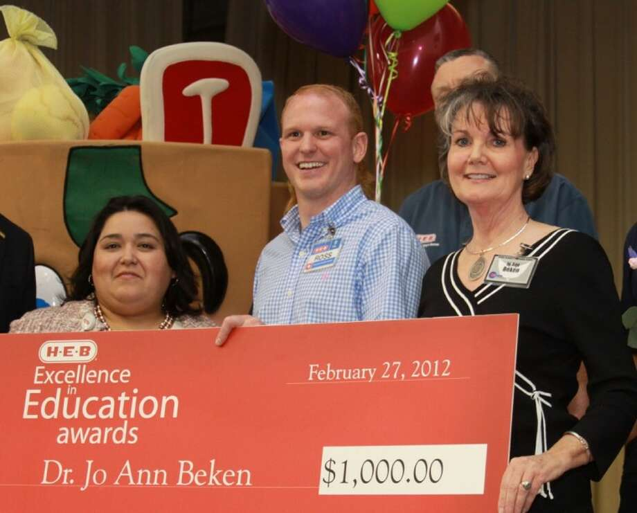 From left, H-E-B financial analyst Erlinda Quintanilla and a colleague pose for a photo with Hauke Alternative School Principal Dr. Jo Ann Beken as she is awarded a $1,000 check and named an H-E-B Excellence in Education Award finalist.